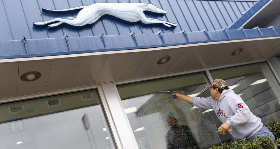 Photo - Jorge Tovar cleans the windows at the new Greyhound bus station at 1948 E Reno. Unlike the Union Bus Station, once controlled by five different bus lines, the new station is controlled by Greyhound, which also coordinates local operations for Jefferson Bus Lines.  Steve Gooch