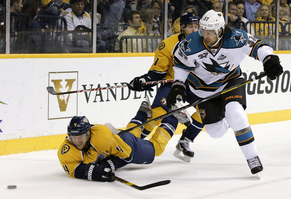 Nashville Predators defenseman Ryan Ellis (4) swings at the puck after being checked by San Jose Sharks right wing Adam Burish (37) during the first period of an NHL hockey game Tuesday, Feb. 12, 2013, in Nashville, Tenn. (AP Photo/Mark Humphrey)