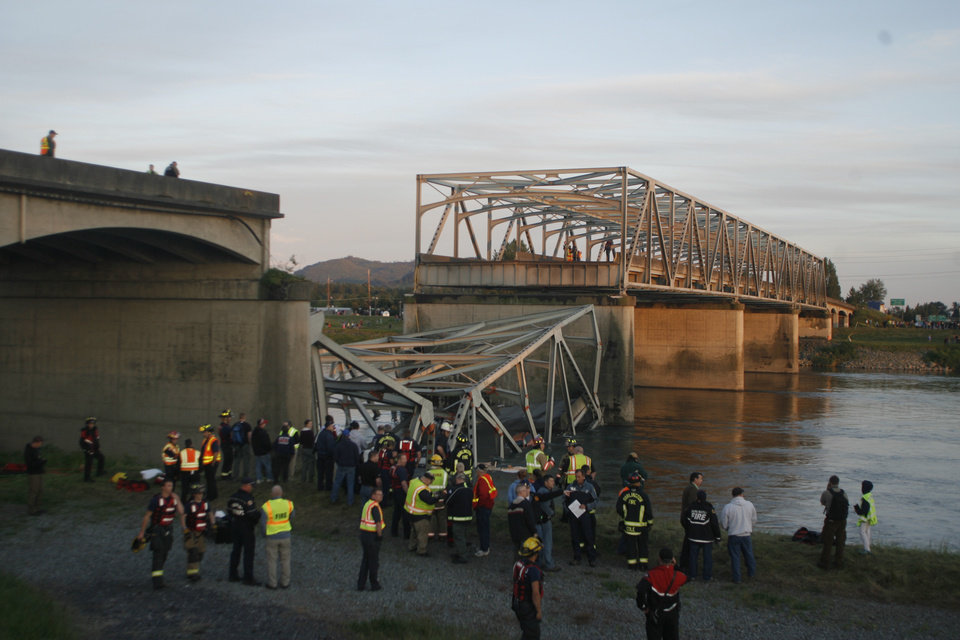 Photo - A portion of the Interstate-5 bridge is submerged after it collapsed into the Skagit river dumping vehicles and people into the water in Mount Vernon, Wash., Thursday, May 23, 2013 according to the Washington State Patrol. (AP Photo/Joe Nicholson)