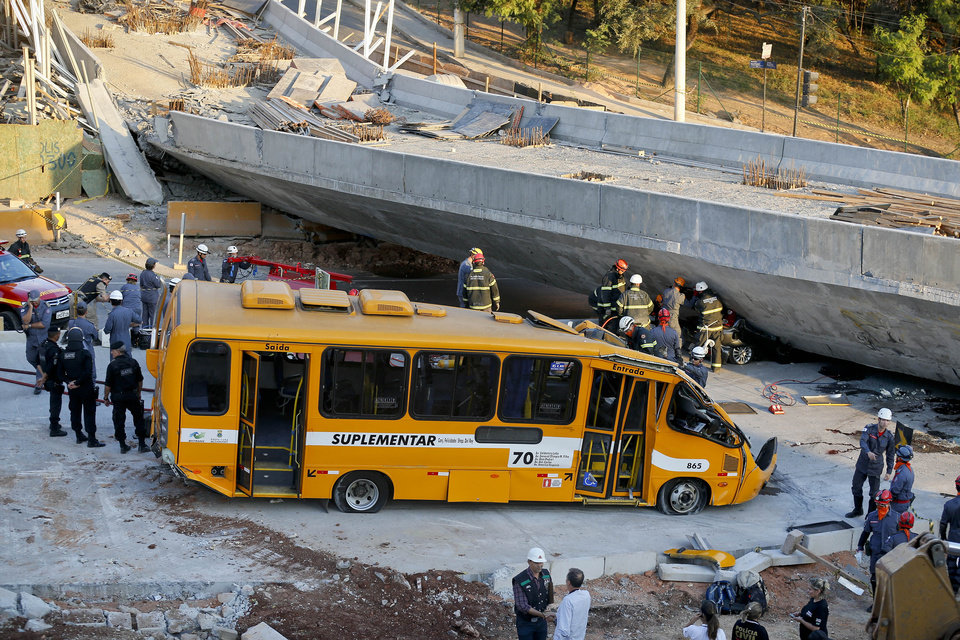 Photo - A bus sits damaged after a bridge collapsed in Belo Horizonte, Brazil, Thursday, July 3, 2014. The overpass under construction collapsed Thursday in the Brazilian World Cup host city. The incident took place on a main avenue, the expansion of which was part of the World Cup infrastructure plan but, like most urban mobility projects related to the Cup, was not finished on time for the event. (AP Photo/Victor R. Caivano)