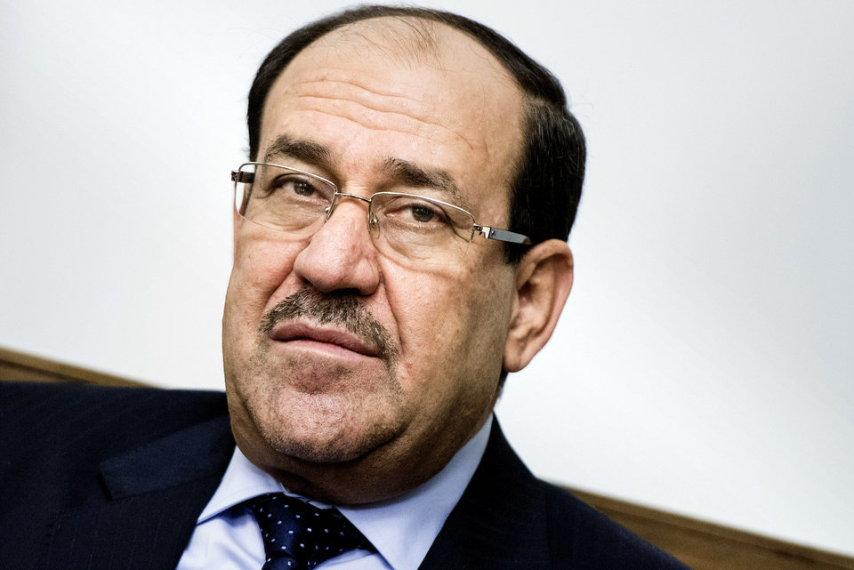 Photo - FILE - In this Monday, June 23, 2014 file photo, Iraqi Prime Minister Nouri al-Maliki meets with U.S. Secretary of State John Kerry in Baghdad.  Iraq's Shiite prime minister on Wednesday, June 25, 2014 rejected calls to form an interim