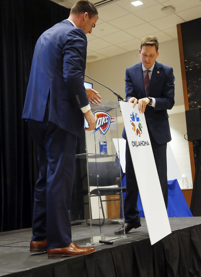 Photo - From left, Gov. Kevin Stitt and Lt. Gov. Matt Pinnell put the new logo in front of the podium during the unveiling of the new brand for Oklahoma at the Oklahoma City Thunder's headquarters inside Chesapeake Energy Arena in Oklahoma City, Wednesday, Feb. 12, 2020. [Nate Billings/The Oklahoman]