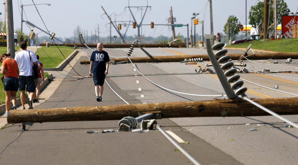 Eric Ponder walks past downed utility lines along N Pennsylvania Avenue just south of NW 150 in Oklahoma City on Sunday, May 19, 2013. Ponder, who lives in a nearby apartment complex without power, is unable to drive his car out of the area due to downed utility lines after storms moved through the area Saturday night. Photo by Bryan Terry, The Oklahoman