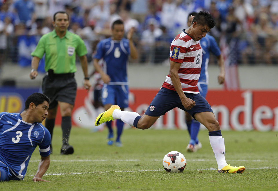 Photo - United States' Joe Corona, right, scores a goal as El Salvador's Victor Turcios Pacheco looks on during the first half in the quarterfinals of the CONCACAF Gold Cup soccer tournament on Sunday, July 21, 2013, in Baltimore. (AP Photo/Patrick Semansky)