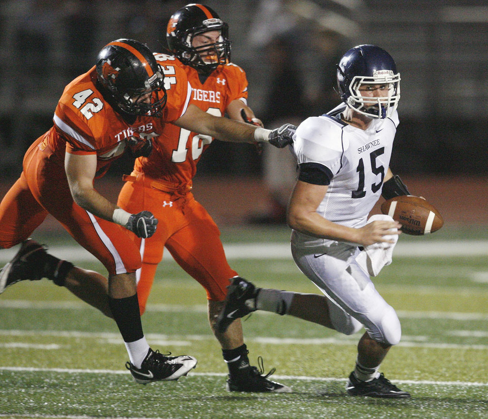 Tigers Roman Wilson (42) and Levi Hudson (18) chase Shawnee quarterback Hunter Holley (15) in high school football at Harve Collins field on Thursday, Sept. 30, 2010, in Norman, Okla.  Photo by Steve Sisney, The Oklahoman
