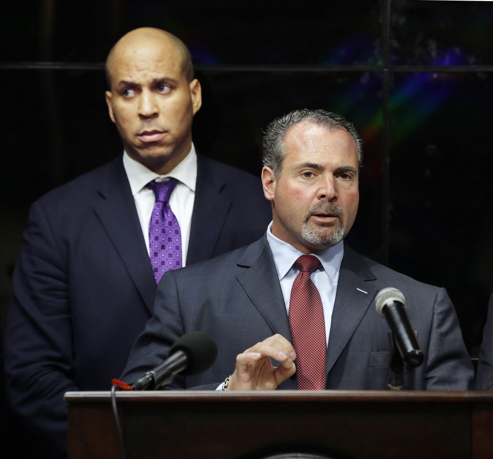 Newark Mayor Cory Booker, left, listens as Police Director Samuel DeMaio, answers a question about arrest of three men after a video surfaced that showed a naked young man being whipped because of his father\'s debt, during a news conference on Wednesday, Feb. 13, 2013. The men identified are 22-year-old Ahmad Holt, 31-year-old Raheem Clark and 23-year-old Jamaar Gray. Police say Holt administered the beating, using a belt provided by Clark. Charges include robbery and aggravated assault. The video shows a 21-year-old man being forced to strip and then whipped with a belt, supposedly because his father owed someone $20. Subsequent to the police investigation, Nicole A. Smith was arrested for drug possession. (AP Photo/Mel Evans)