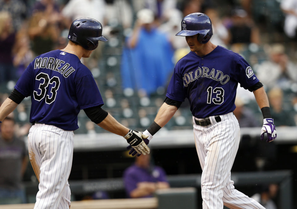 Photo - Colorado Rockies' Drew Stubbs (13) is congratulated by teammate Justin Morneau (33) after hitting a solo home run off San Diego Padres starting pitcher Ian Kennedy during the fourth inning of an MLB baseball game on Monday, July 7, 2014, in Denver (AP Photo/Jack Dempsey)