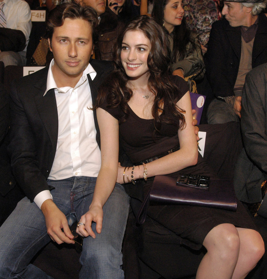 "FILE - In this Feb. 3, 2008, file photo, actress Anne Hathaway, right, sits with her boyfriend, Raffaello Follieri, at the Miss Sixty fashion show during fashion week in New York. Follieri was released Friday morning from a prison in Loretto, 80 miles east of Pittsburgh. Follieri pleaded guilty to cheating investors by falsely claiming he had Vatican connections that enabled him to buy church property at a discount. He was sentenced in 2008 to 4 1/2 years in prison. Follieri agrees he owes more than $3.6 million to those he ripped off. The proceeds supported a playboy lifestyle that included a $37,000-a-month New York City apartment and lavish vacations with Hathaway, the star of ""The Princess Diaries."" (AP Photo/Brian McDermott)"