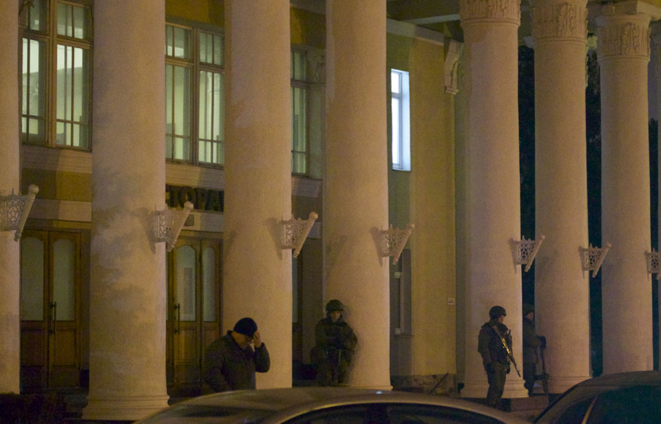 Photo - Unidentified armed men guard a building at the airport in Simferopol, Ukraine, on Friday, Feb. 28, 2014. Dozens of armed men in Russian-style military uniforms occupied the airport in the capital of Ukraine's strategic Crimea region early Friday. (AP Photo/Ivan Sekretarev)