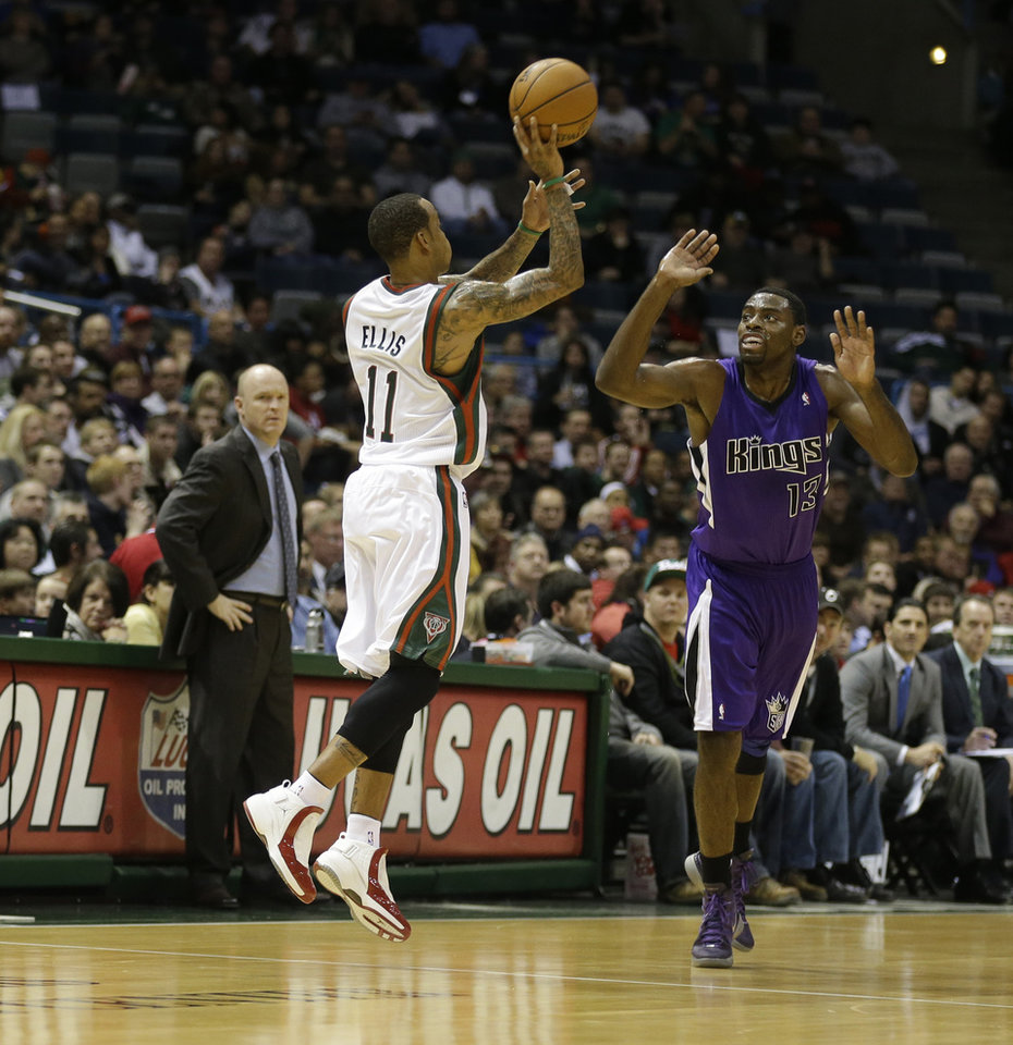 Milwaukee Bucks\' Monta Ellis (11) hits a half-court shot at the end of the first quarter as Sacramento Kings\' Tyreke Evans(13) defends during a NBA basketball game on Wednesday, Dec. 12, 2012, in Milwaukee. Bucks head coach Scott Skiles, left, watches the play. (AP Photo/Jeffrey Phelps)
