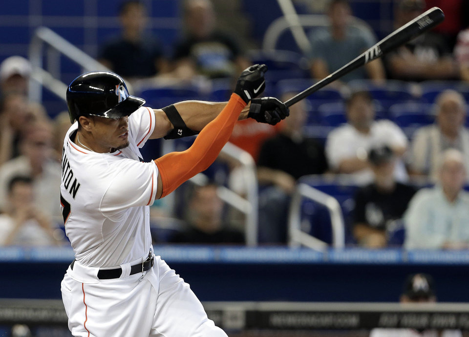 Photo - Miami Marlins' Giancarlo Stanton hits a double in the first inning of a baseball game against the Colorado Rockies, Thursday, April 3, 2014, in Miami. (AP Photo/Lynne Sladky)