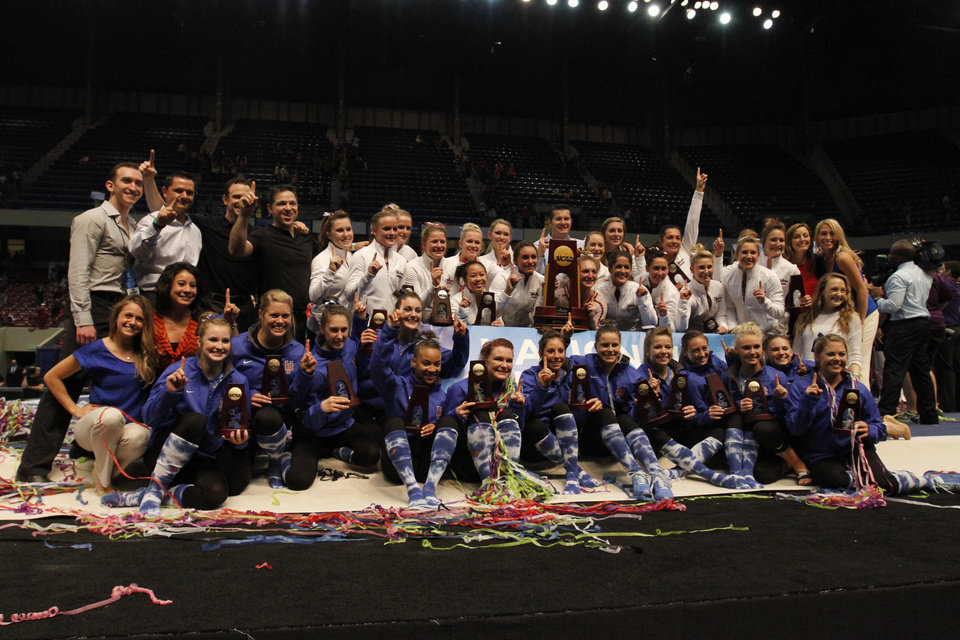 Photo - Florida and Oklahoma celebrate as co-champions during the NCAA college women's gymnastics championships on Saturday, April 19, 2014, in Birmingham, Ala. (AP Photo/Butch Dill)