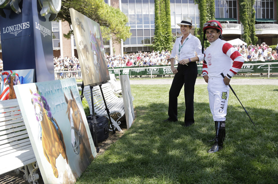 Photo - Jockey Victor Espinoza, right, looks over artwork by Susan Sommer-Luarca before riding in an undercard race at Belmont Park, Saturday, June 7, 2014, in Elmont, N.Y. Espinoza will ride favorite California Chrome in the Belmont Stakes later in the day. (AP Photo/Mark Lennihan)