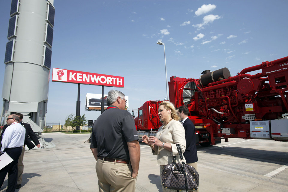 Photo - Gov. Mary Fallin, right, speaks with a Halliburton representative at the  demonstration in Oklahoma City about how Halliburton  is incorporating compressed natural gas in its operations. Photo by Aliki Dyer, The Oklahoman  Aliki Dyer - The Oklahoman