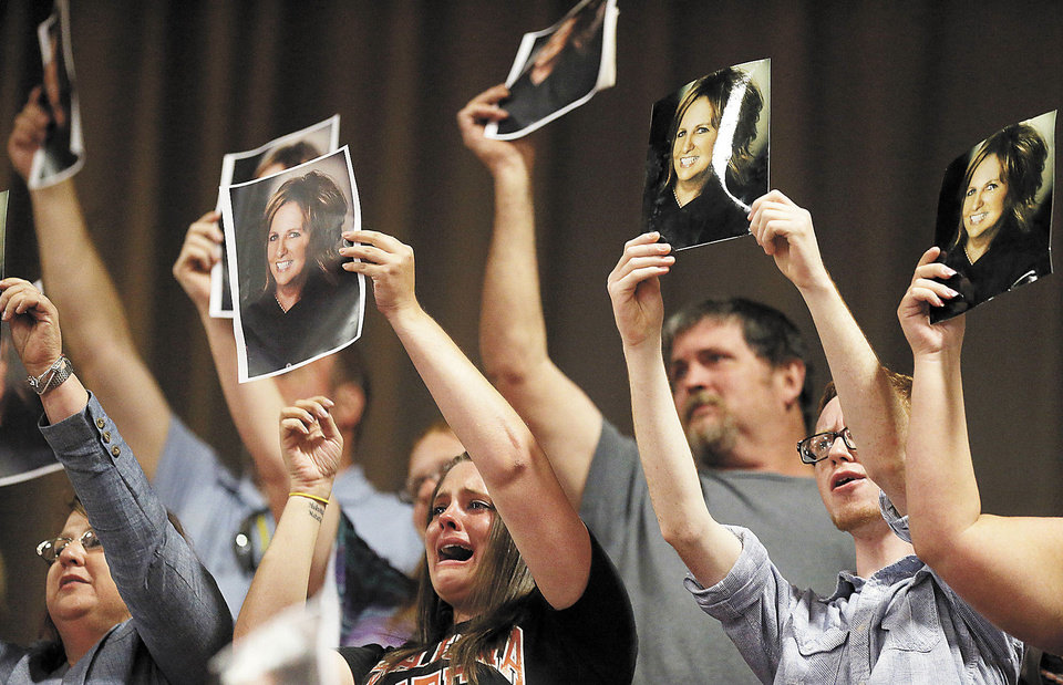 Photo - Friends and family cheer as they hold a picture of Terri Long when her daughter Alyson Costilla graduates from Southmoore at the Cox Convention Center, Saturday, May 25, 2013. Photo by Sarah Phipps, The Oklahoman