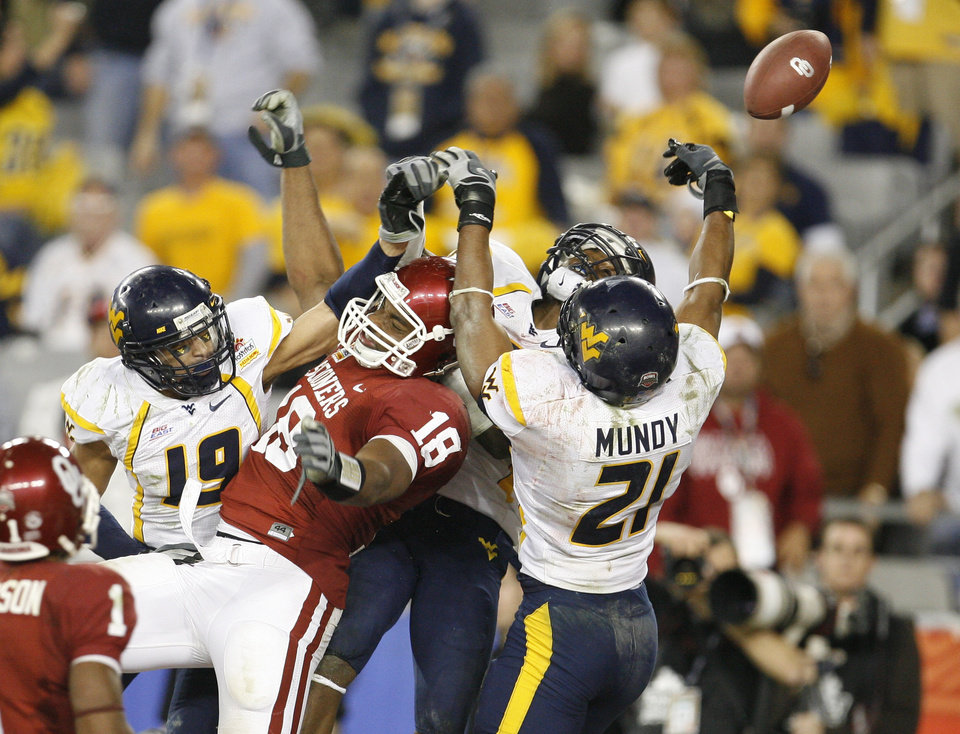 Photo - OU's Jermaine Gresham battles for the ball between Vaughn Rivers, left, Eric Wicks, andRyan Mundy of West Virginia during the second half of the Fiesta Bowl college football game between the University of Oklahoma Sooners (OU) and the West Virginia University Mountaineers (WVU) at The University of Phoenix Stadium on Wednesday, Jan. 2, 2008, in Glendale, Ariz. 