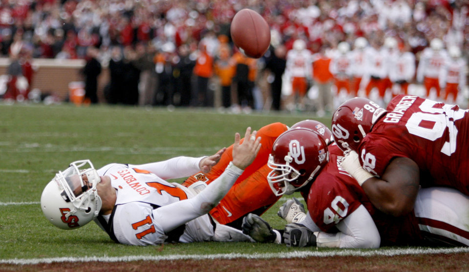 Photo - OSU's Zach Robinson fumbles the ball after being hit by OU's Curtis Lofton, center, and DeMarcus Granger during the first half of the college football game between the University of Oklahoma Sooners (OU) and the Oklahoma State University Cowboys (OSU) at the Gaylord Family-Memorial Stadium on Saturday, Nov. 24, 2007, in Norman, Okla.  Photo By Bryan Terry, The Oklahoman