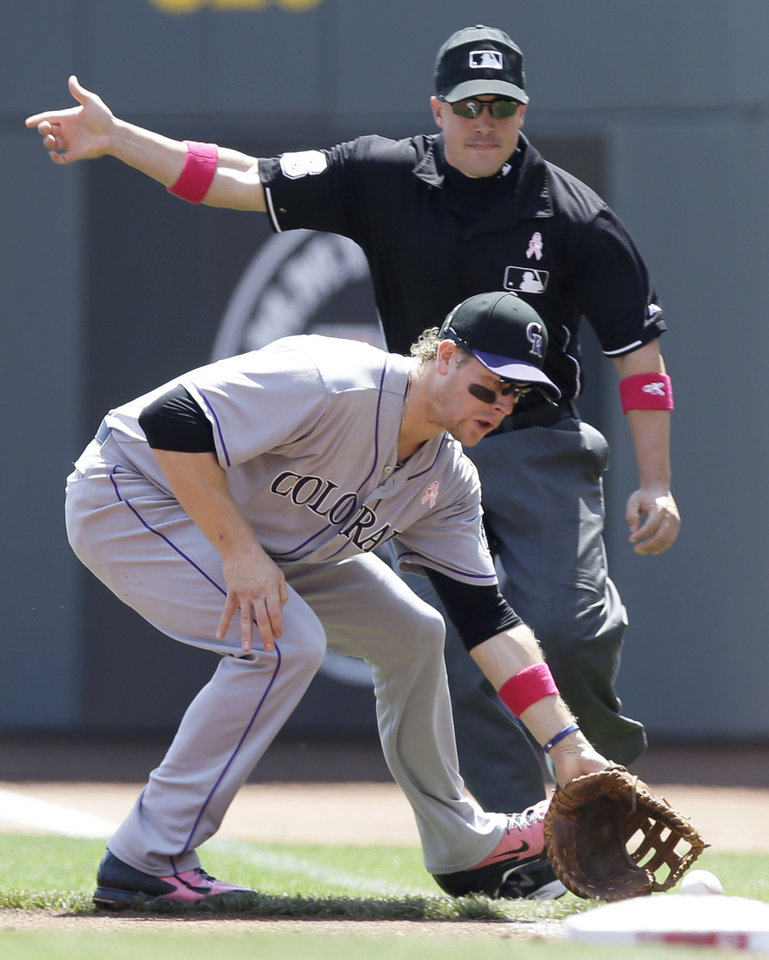 Photo - Colorado Rockies first baseman Justin Morneau fields a ball hit by Cincinnati Reds' Joey Votto that was ruled fair by umpire Chris Segal, rear, in the first inning of a baseball game, Sunday, May 11, 2014, in Cincinnati. Morneau touched first for the out. (AP Photo/Al Behrman)