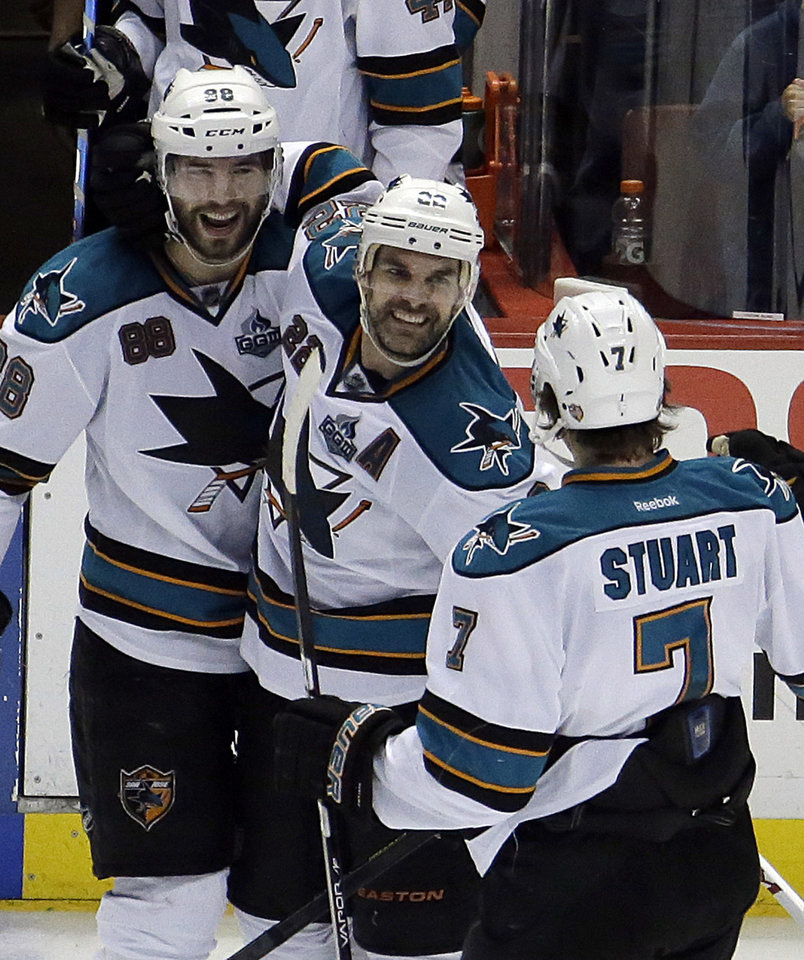 San Jose Sharks defenseman Dan Boyle (22), center, is congratulated by teammates Brent Burns (88) and Brad Stuart (7) on his empty-net goal from center ice against the Anaheim Ducks in the third period of an NHL hockey game in Anaheim, Calif., Monday, March 25, 2013. The Sharks won, 5-3. (AP Photo/Reed Saxon)