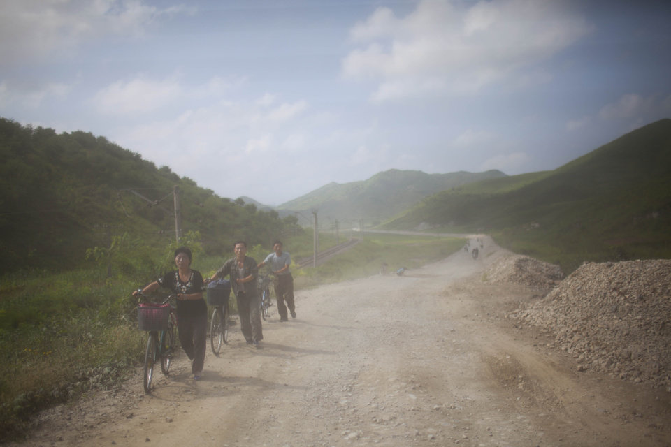 Photo -   In this Monday, Aug 13, 2012 photo, North Koreans are dusted by passing vehicles as they push their bicycles down a dirt road in Songchon County, North Korea. Twin typhoons are renewing fears of a humanitarian crisis in North Korea, where poor drainage, widespread deforestation and fragile infrastructure can turn even a routine rainstorm into a catastrophic flood. (AP Photo/David Guttenfelder)