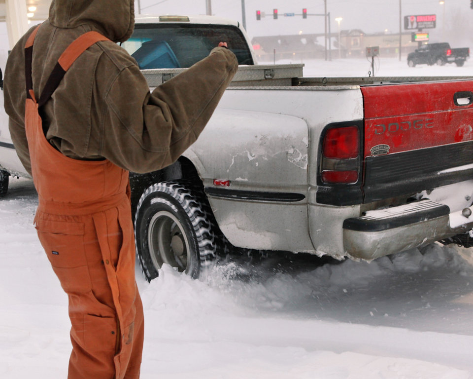 Photo - A man helps the driver of this truck get unstuck in the parking lot of a convenience store near SE 15 and Post Rd. in Midwest City. A winter storm created whiteout conditions and caused snow drifts that made problems for the few motorists who ventured out Tuesday morning, Feb. 1, 2011.   Photo by Jim Beckel, The Oklahoman