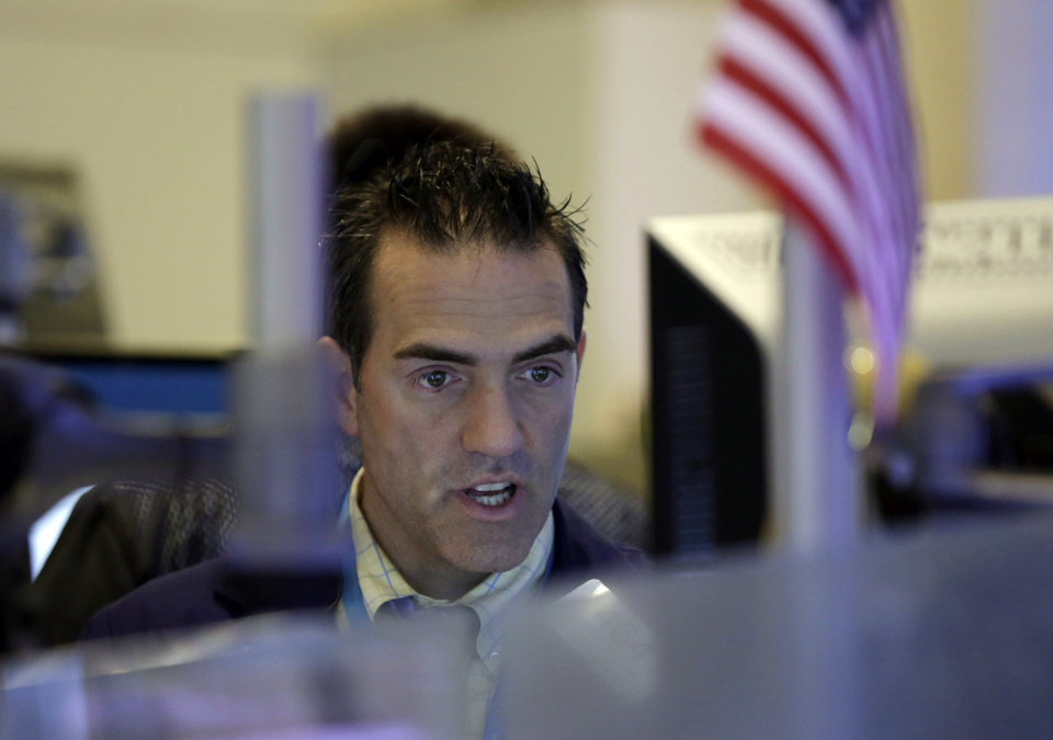 Photo - Trader Gregory Rowe checks a monitor in a booth on the floor of the New York Stock Exchange Friday, Aug. 1, 2014.  U.S. markets steadied on Friday a day after a major sell-off. Investors focused on a relatively strong jobs report, which showed the U.S. economy created 209,000 jobs in July, the sixth straight month of job growth above 200,000. (AP Photo/Richard Drew)