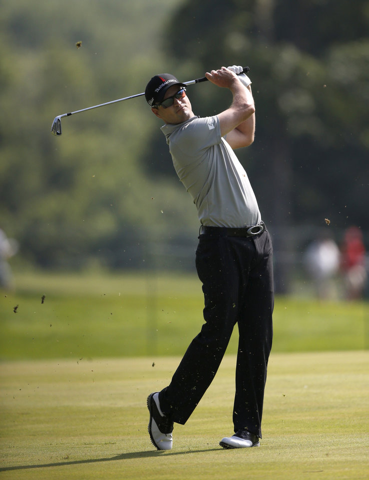 Photo - Zach Johnson watches his approach attempt on the 18th fairway during the first round of the 2014 John Deere Classic golf tournament at TPC Deere Run in Silvis, Ill., Thursday, July 10 2014. (AP Photo/Charles Rex Arbogast)