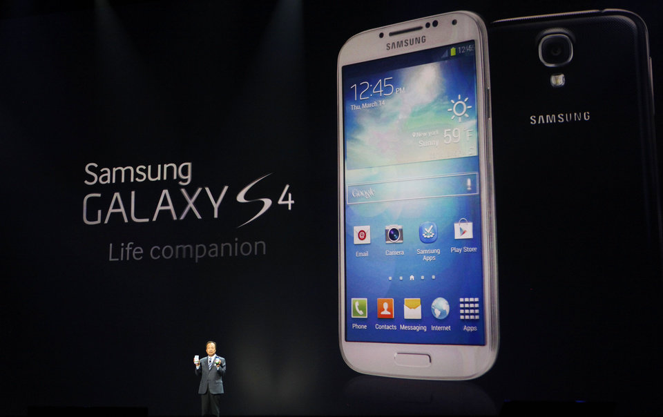 Photo - JK Shin, President and Head of IT and Mobile Communications for Samsung Electronics, presents the new Samsung Galaxy S 4 during the Samsung Unpacked event at Radio City Music Hall, Thursday, March 14, 2013 in New York.  (AP Photo/Jason DeCrow)