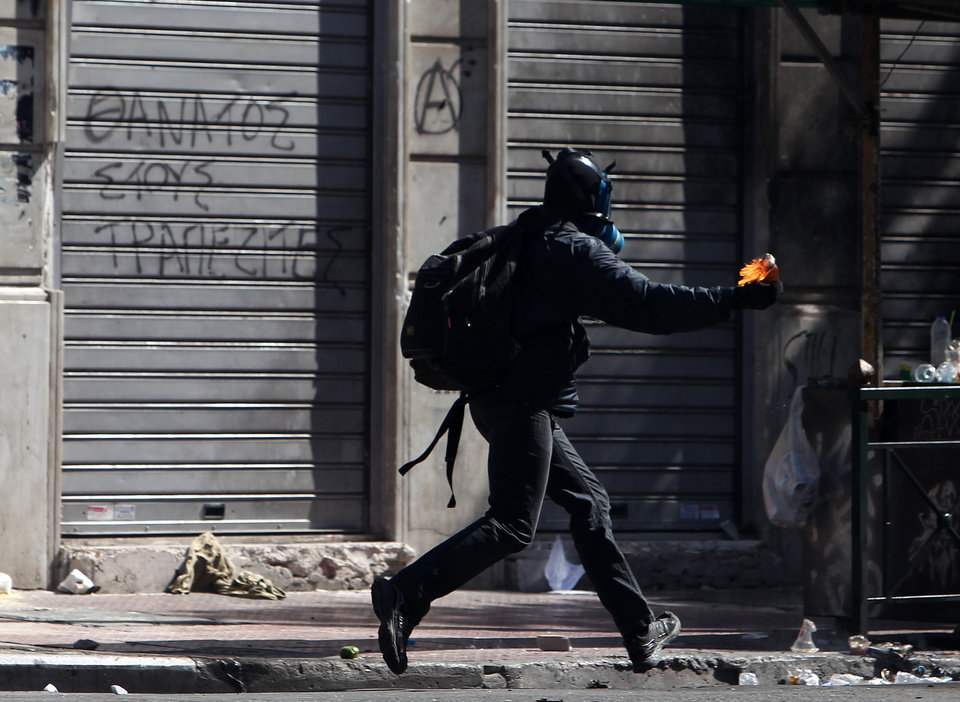 Photo -   A protester prepares to throw a petrol bomb at riot police during a nationwide general strike in Athens, Wednesday, Sept. 26, 2012. Police clashed with protesters hurling petrol bombs and bottles in central Athens Wednesday after an anti-government rally called as part of a general strike in Greece turned violent. About 50,000 people joined the union-organized march in central Athens on Wednesday, held during a general strike against new austerity measures planned in the crisis-hit country. (AP Photo/Thanassis Stavrakis)