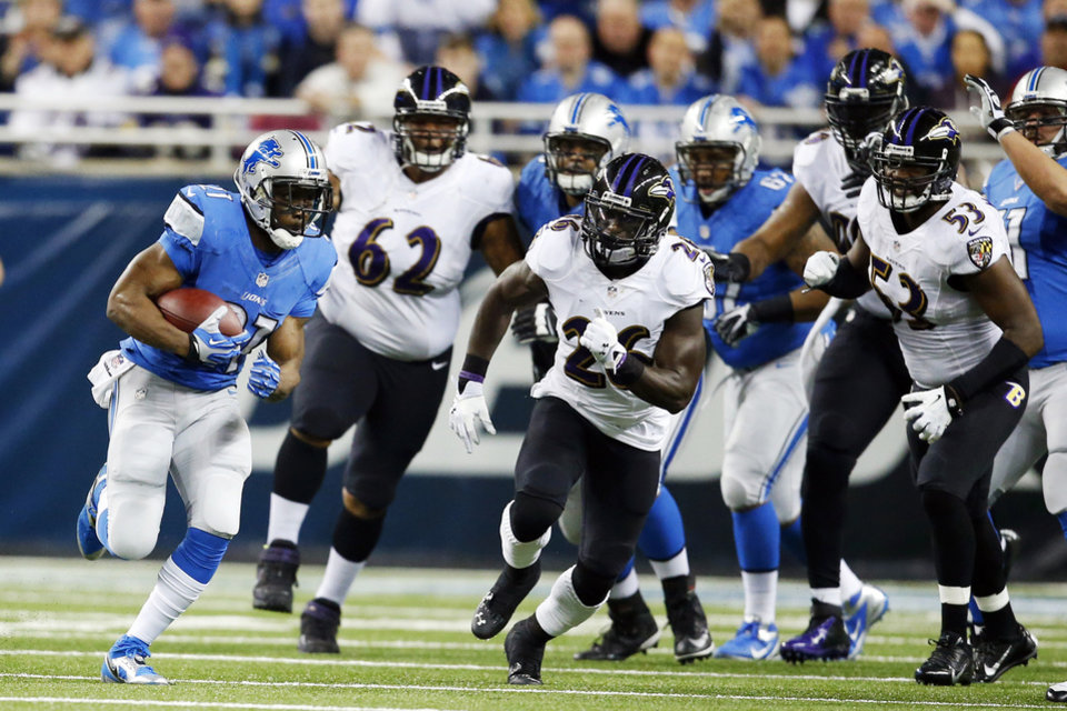 Photo - Detroit Lions running back Reggie Bush, left, pulls away from the Baltimore Ravens defense during the first quarter of an NFL football game in Detroit, Monday, Dec. 16, 2013. (AP Photo/Rick Osentoski)