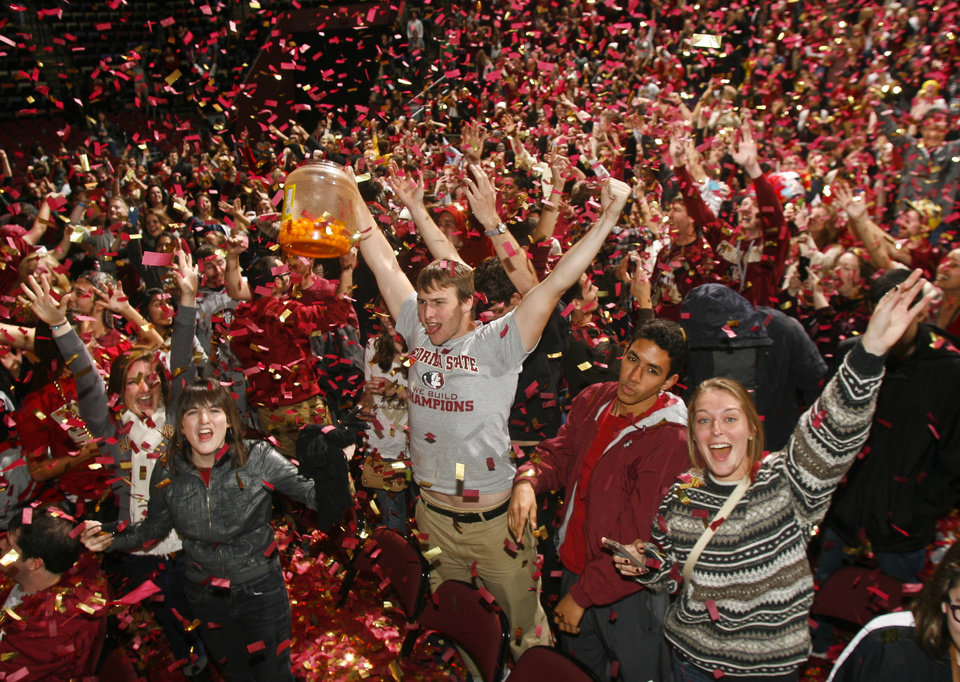 Photo - Florida State fans react as confetti rains down on them after watching the BCS Championship football game against Auburn on a 30-foot screen at the Tallahassee Leon County Civic Center on Monday, Jan. 6, 2014, in Tallahassee, Fla. Florida State beat Auburn 34-31. (AP Photo/Phil Sears)