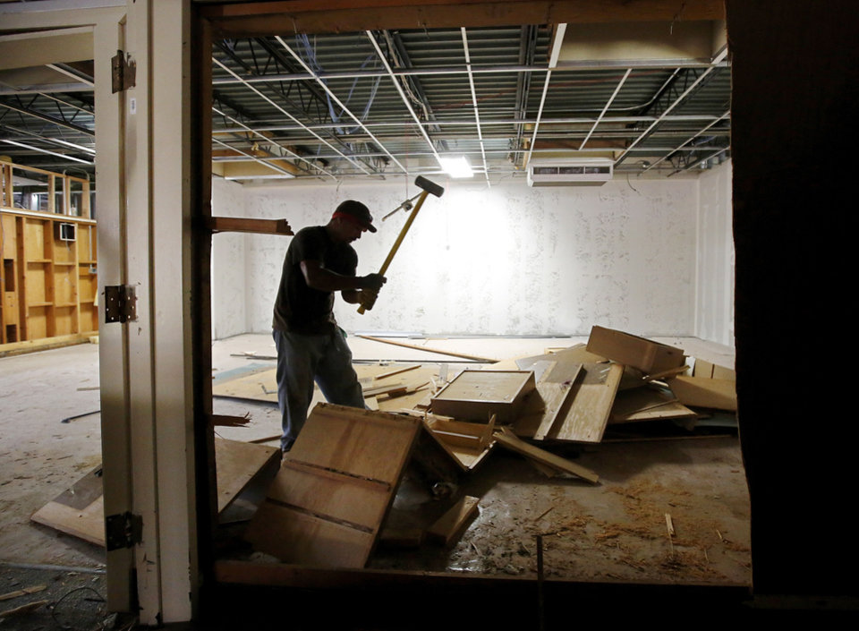Photo - A man uses a sledgehammer  to break up interior walls and cabinets at Moore's Central Junior High School. Work is being done at the school to accommodate elementary students displaced by the May 20 tornado.    Photo  by Jim Beckel, The Oklahoman.  Jim Beckel - THE OKLAHOMAN