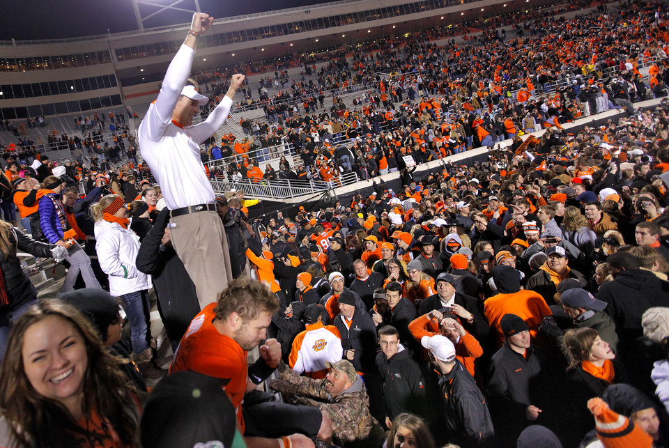 Oklahoma State receiver coach Doug Meacham celebrates the 44-10 win over Oklahoma during the Bedlam college football game between the Oklahoma State University Cowboys (OSU) and the University of Oklahoma Sooners (OU) at Boone Pickens Stadium in Stillwater, Okla., Saturday, Dec. 3, 2011. Photo by Chris Landsberger, The Oklahoman