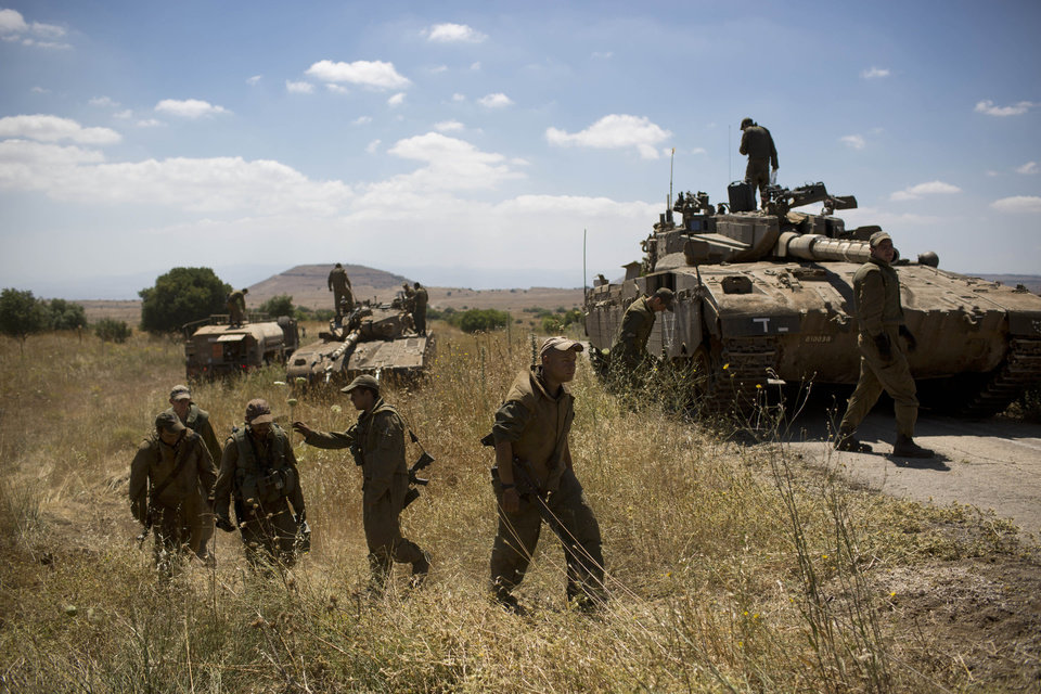 Photo - Israeli soldiers work on their tanks following the first death on the Israeli side of the Golan since the Syrian civil war erupted more than three years ago, near the Israeli village of Alonei Habashan, in the area of Tel Hazeka, close to the Quneitra border crossing in the Israeli-controlled Golan Heights, Sunday, June 22, 2014.  A civilian vehicle in the Israeli-controlled Golan Heights was targeted by forces in neighboring Syria on Sunday in an attack that killed a 15-year-old boy and prompted Israeli tanks to retaliate by firing on Syrian government targets, the Israeli military said. (AP Photo/Oded Balilty)