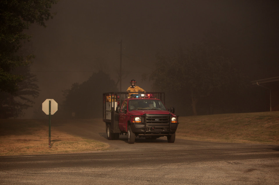 Photo - Firefighters work the scene of a wildfire in Luther, Okla., Friday, Aug. 3, 2012. Photo by Sarah Phipps, The Oklahoman