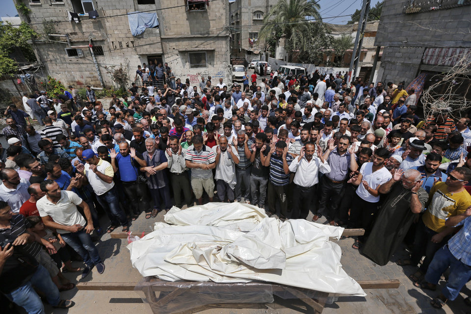 Photo - Mourners pray in front of the bodies of seven members of the Kelani family, killed overnight by an Israeli strike in Gaza City, during their funeral in Beit Lahiya, northern Gaza Strip, on Tuesday, July 22, 2014. Ibrahim Kelani, 53, his wife Taghreed and their five children, were killed in the strike on a Gaza City highrise. Ibrahim's brother Saleh Kelani said Tuesday that his brother and his brother's children, ranging in age from four to 12, had German citizenship, while his wife had not. The family had rented the apartment in the high-rise after fleeing their home in the northern Gaza town of Beit Lahiya which came under heavy shelling by the Israeli army. (AP Photo/Lefteris Pitarakis)
