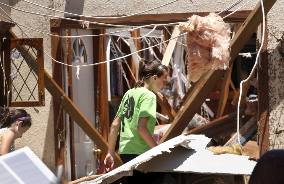 Photo - People arrived at Fred and JoAnn Horn's home to help in their salvage efforts. Two girls walk through debris in the front part of the house as they make their way to a back bedroom. Fred and JoAnn Horn have lived in their home at 4924 SW 15 in El Reno since 1978. He is a retired state trooper and now serves as a deputy for the Canadian County Sheriff's Department.  Their home was heavily damaged in  Friday night's tornado. More than two dozen family members, church friends and neighbors came to the Horn's home on Saturday, June 1, 2013, to help recover items that can be saved. Fred and JoAnn were in a neighbor's cellar with 10 others when the tornado ravaged homes in the area. Fred said he saw the twisters as they approached--