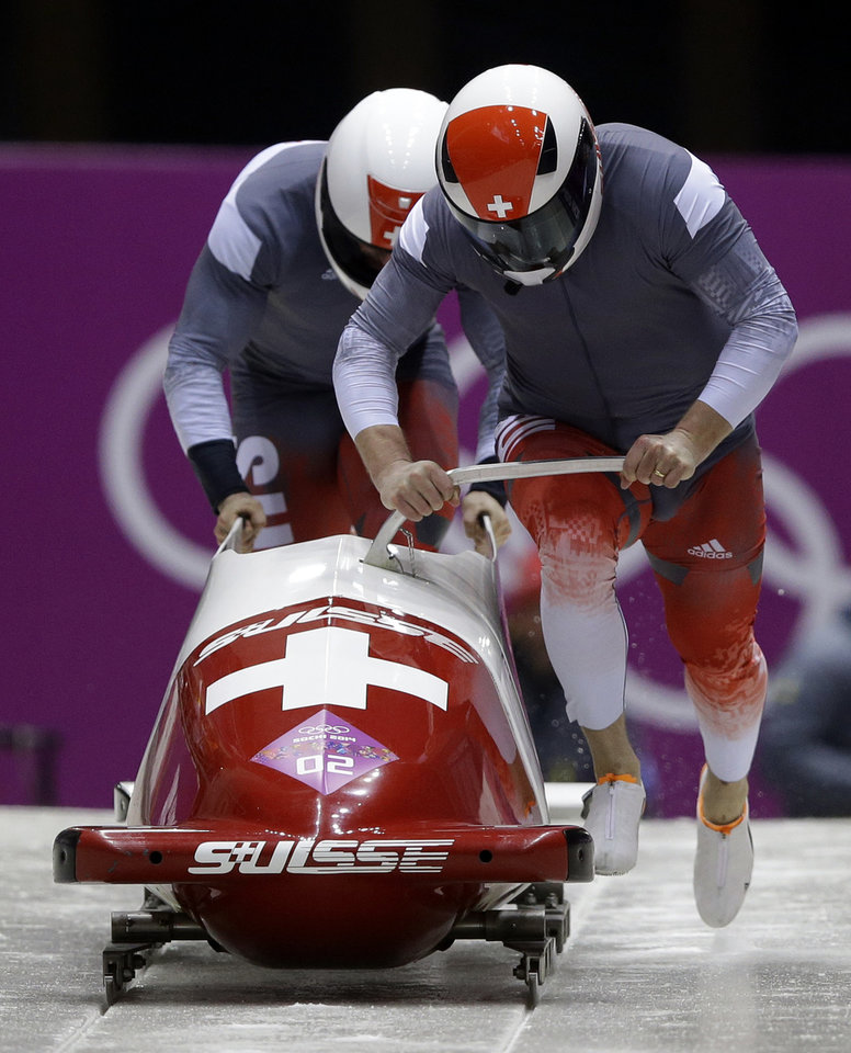 Photo - The team from Switzerland SUI-1, piloted by Beat Hefti and brakeman Alex Baumann, start their first run during the men's two-man bobsled competition at the 2014 Winter Olympics, Sunday, Feb. 16, 2014, in Krasnaya Polyana, Russia. (AP Photo/Dita Alangkara)