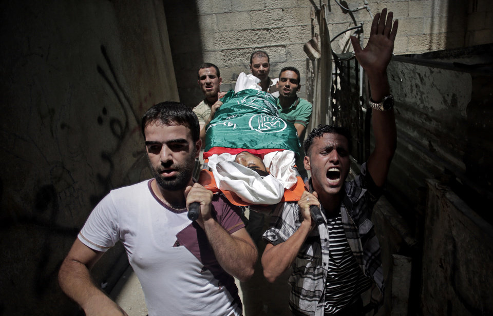 Photo - Palestinian relatives of Mohammed Naser, chant slogans as they carry his lifeless body to the family house during his funeral in the Khan Younis refugee camp in the southern Gaza Strip, Saturday, July 19, 2014. Naser and eight others were killed in an early morning Israeli missile strike, official said. (AP Photo/Khalil Hamra)