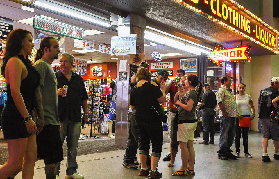 In this May 22, 2014 photo, People gather outside a convenience store, with drinks they purchased inside, at the Fremont Street Experience in Las Vegas.  Las Vegas officials are banning people from drinking out of aluminum cans and glass bottles at the Fremont Street Experience, saying they want to cut down on the rowdy revelry that has led to fights and even a shooting that wounded two people last summer. An ordinance passed Wednesday, June 18, 2014 by the City Council aims to discourage people from getting drunk on cheap liquor from the souvenir stores along the pedestrian mall, and push them to buy more expensive drinks poured into cups at casinos and restaurants flanking the attraction. (AP Photo/Las Vegas Review-Journal, Jason Bean) LOCAL TV OUT; LOCAL INTERNET OUT; LAS VEGAS SUN OUT