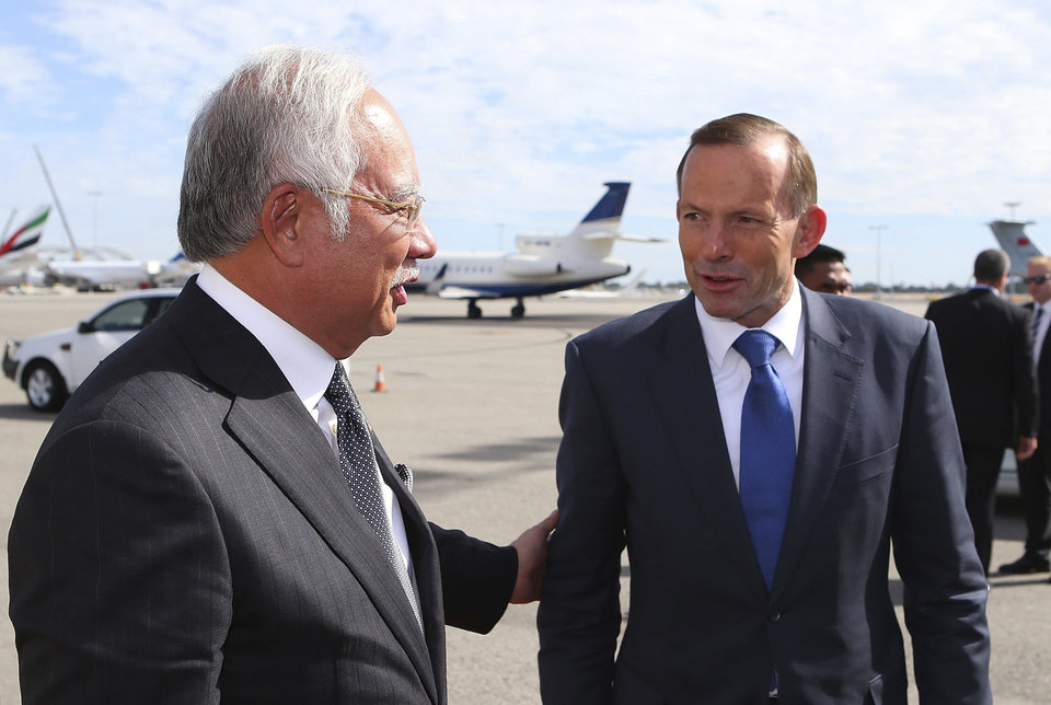 Photo - FILE - In this April 3, 2014 file photo, Australian Prime Minister Tony Abbott, right, chats with his Malaysian counterpart Najib Razak at Perth International Airport as Razak prepares to depart Australia after his visit during the search of the missing Malaysia Airlines flight MH370, in Perth, Australia. The leaders of Malaysia and Australia have used warm and glowing terms to assure the world that their partnership in the desperate hunt for the missing airliner is built on a firm and abiding friendship. But it's also an odd-couple relationship that has proved brittle in the past and has been blighted by hostility, rivalries and cultural misunderstandings. (AP Photo/Paul Kane, File)