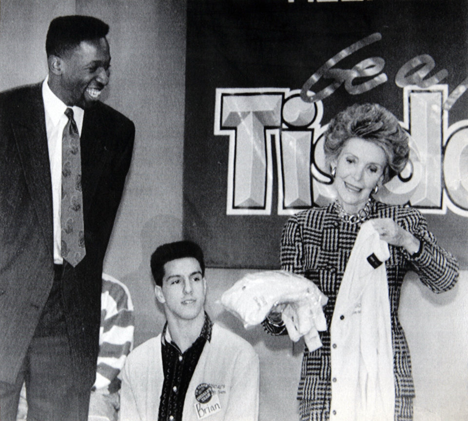 "Former OU basketball player Wayman Tisdale. INDIANAPOLIS, Feb. 4 - TEAM MEMBER - Indiana Pacer Wayman Tisdale (left) presents first lady Nancy Reagan with Tisdale Team sweaters at Howe High School in Indianapolis Thursday. Watching is Howe student Brian McDonald. Mrs. Reagan came to town to honor Tisdale and his ""team,"" a group of high schoolers who talk to youngsters about resisting the pressure to try drugs. (aP laserphoto) (stf-Chuck Robinson) 1988. 2-10-88 ORG XMIT: KOD"