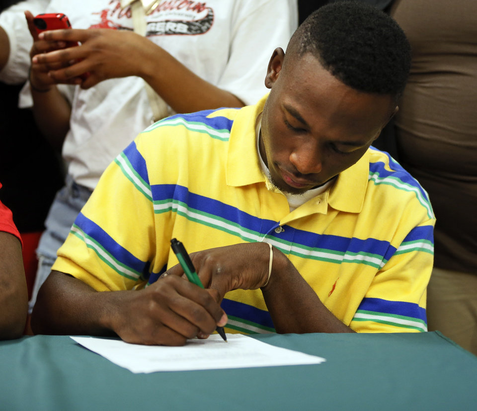 Photo - Cornelius Fugett signs to play football at Panhandle State during the signing day ceremony at Edmond Santa Fe High School in Edmond, Okla., Wednesday, Feb. 6, 2013. Photo by Nate Billings, The Oklahoman