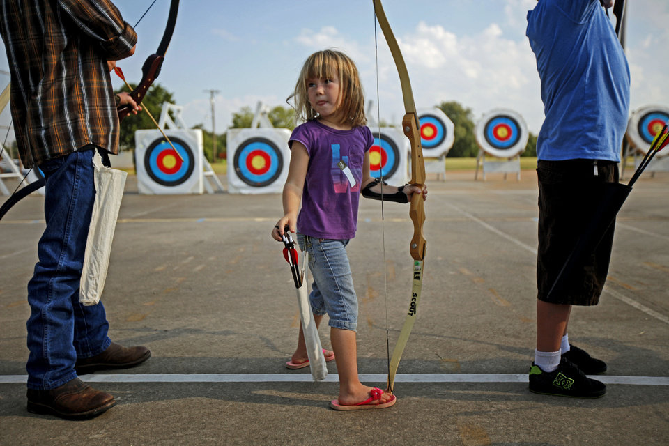 Photo - Hope White, 6, of Norman stands at the shooting line during a Junior Olympic Archery Development Club shoot put on by the Trosper Archery Club on Saturday, August 24, 2013, at Trosper Park in Oklahoma City. This was Hope's first time shooting as she and over 60 participants, from beginners to intermediates, that took part in the shoot which takes place every Saturday. For $5 each person is supplied with equipment and instruction starting at 9am for beginners and 10am for intermediate shooters. Photo by Bryan Terry, The Oklahomane