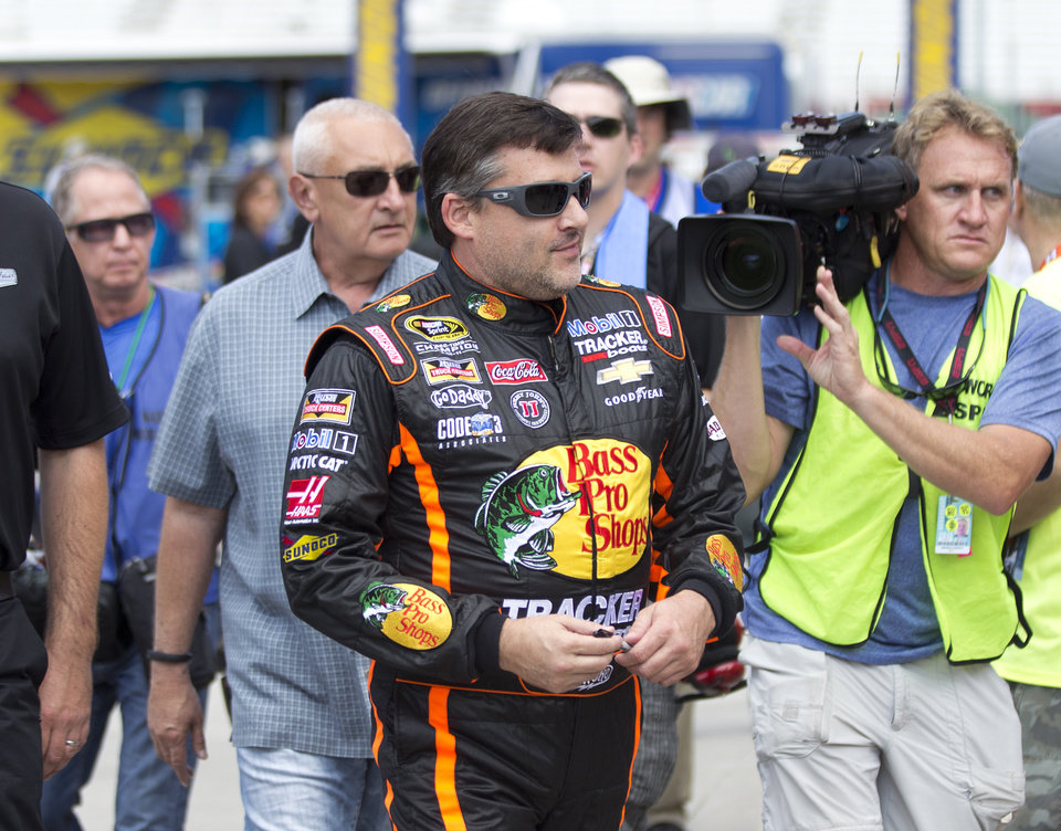 Photo - NASCAR driver Tony Stewart walks to his car during practice for Sunday's NASCAR auto race at Atlanta Motor Speedway in Hampton, Ga., Friday, Aug. 29, 2014. Sunday's race will be his first since his car struck and killed a fellow driver during a sprint race in New York three weeks ago. (AP Photo/John Bazemore)