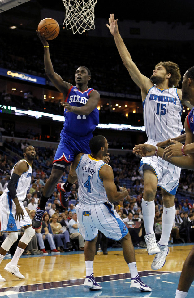 Philadelphia 76ers point guard Jrue Holiday (11) drives to the basket as New Orleans Hornets shooting guard Xavier Henry (4) draws an offensive foul in the first half of an NBA basketball game in New Orleans, Wednesday, Nov. 7, 2012. (AP Photo/Gerald Herbert)