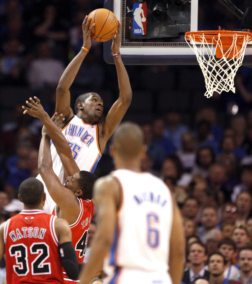 Photo - Oklahoma City's Kevin Durant dunks the ball over Chicago's Kurt Thomas and C.J. Watson(32) during the NBA season opener basketball game between the Oklahoma City Thunder and the Chicago Bulls in the Oklahoma City Arena on Wednesday, Oct. 27, 2010. Photo by Sarah Phipps, The Oklahoman