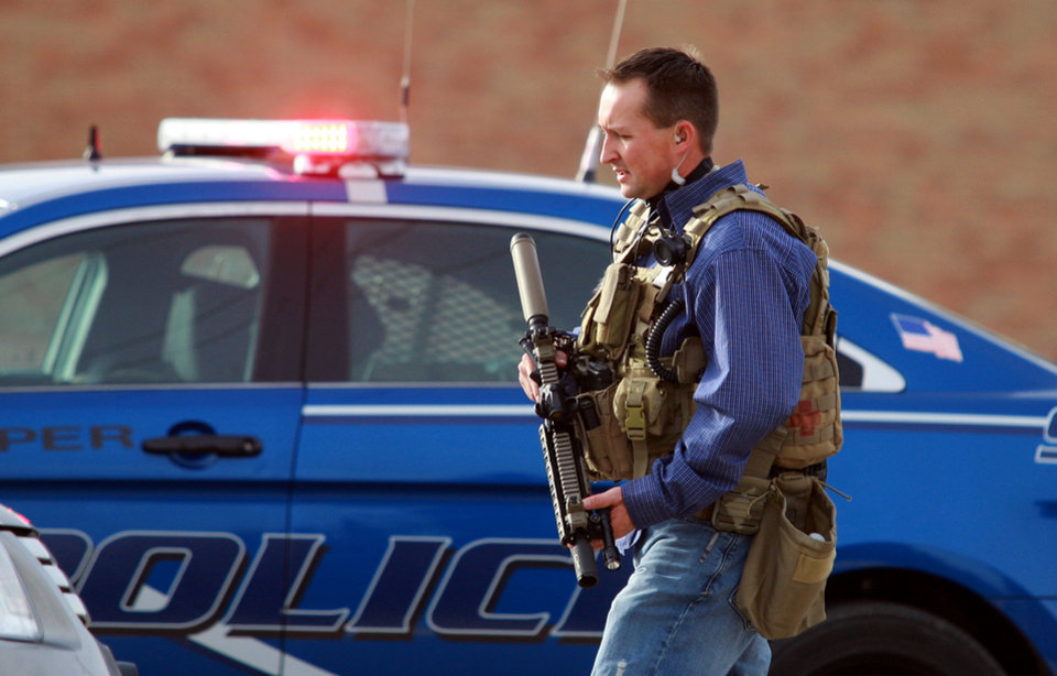 Photo - A Natrona County Sheriff's deputy in tactical gear leaves the scene of a reported homicide at Casper College on Friday morning, Nov. 30, 2012, in Casper, Wyo. At least one person was killed and another was wounded Friday in an attack at Casper College, a community college in central Wyoming. It happened around 9 a.m., said school spokesman Rich Fujita.  (AP Photo/Casper Star-Tribune, Alan Rogers) MANDATORY CREDIT  TRIB.COM