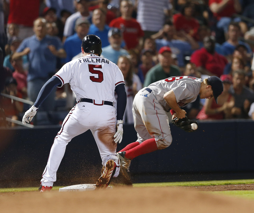 Photo - Atlanta Braves' Freddie Freeman arrives at third with a triple as Boston Red Sox third baseman Brock Holt (26) handles the wide throw in the fifth inning of a baseball game Tuesday, May 27, 2014, in Atlanta. (AP Photo/John Bazemore)