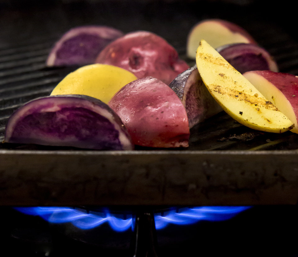 Photo - For a wonderful smoky flavor, put potato halves in a microwave-safe bowl; microwave, covered, until just tender. Cool slightly; coat lightly with olive oil. Grill 5 to 7 minutes, turning occasionally. (Bill Hogan/Chicago Tribune/MCT)